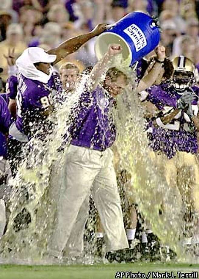 Washington coach Rick Neuheisel is doused by Marcus Roberson (98) in the final seconds against Purdue during the 87th in Pasadena, Calif., Monday, Jan. 1, 2001. Washington defeated Purdue, 34-24. (AP Photo/Mark J. Terrill) Photo: MARK J. TERRILL