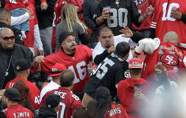 """In this photo made Saturday, Aug. 20, 2011, football fans fight in the stands during a preseason NFL football game between the San Francisco 49ers and the Oakland Raiders in San Francisco. After two men were shot and wounded following the San Francisco 49ers-Oakland Raiders preseason game, the NFL and the mayors of the two cities jointly called for an end to """"intimidation"""" and acts of violence at sporting events."""