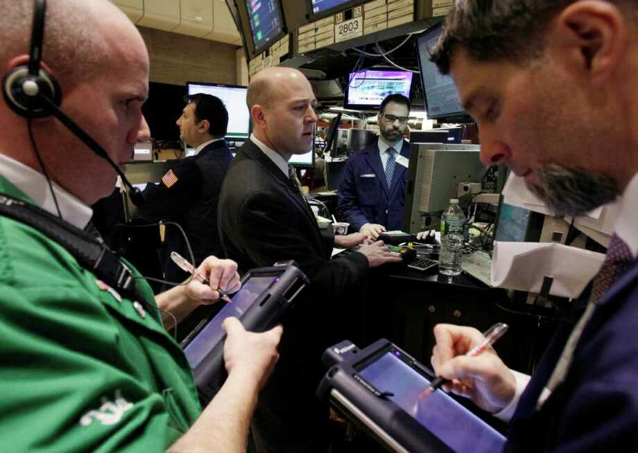 In this Feb. 1, 2012 photo, specialist Jay Woods, center, works at his post on the floor of the New York Stock Exchange. Markets took a breather on Thursday, Feb. 2, 2012, following solid gains in the previous session, as investors positioned themselves for crucial U.S. jobs data that often set the tone for a week or two after their release. (AP Photo/Richard Drew) Photo: Richard Drew
