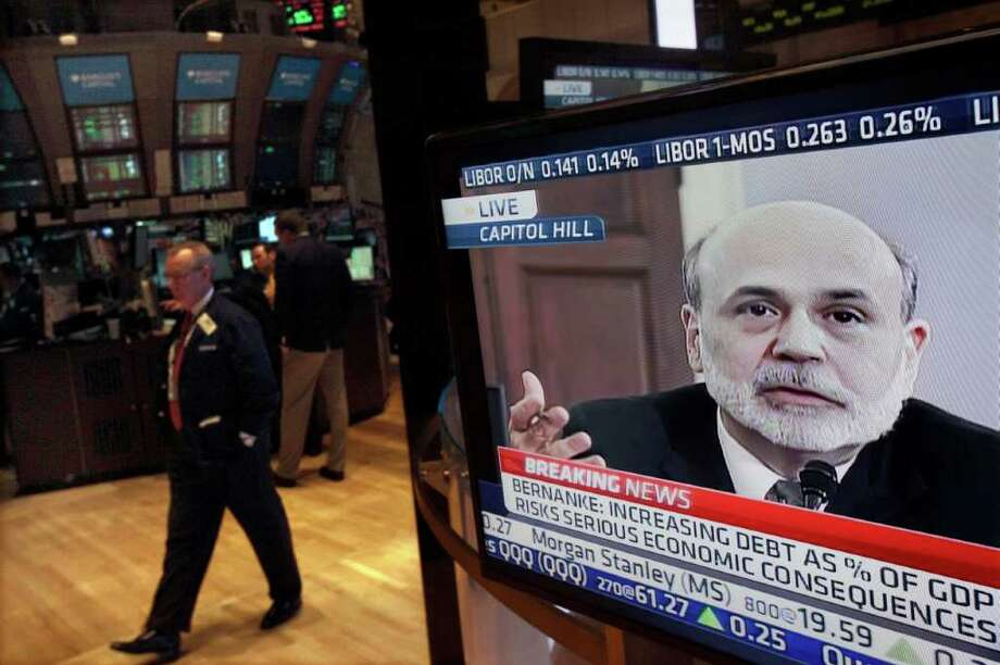 Federal Reserve Chairman Ben Bernanke's testimony before the House Budget Committee is visible on a television screen on the floor of the New York Stock Exchange Thursday, Feb. 2, 2012. Bernanke is urging lawmakers to balance their desire to cut deficits with policies that could help boost the weak economy in the short run. (AP Photo/Richard Drew) Photo: Richard Drew