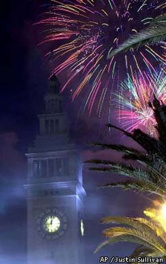 Fireworks burst above the Ferry Building moments after midnight. Associated Press photo by Justin Sullivan