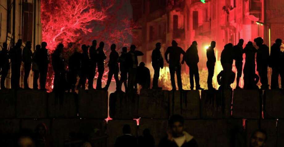 Egyptian protesters stand on a cement block barrier separating the interior ministry from Tahrir Square, Cairo, Egypt Thursday, Feb. 2, 2012. Egyptian police fired tear gas Thursday at thousands of demonstrators outside the Interior Ministry protesting the security forces' failure to prevent a soccer riot that killed more than 70 people.(AP Photo/Khalil Hamra) Photo: Khalil Hamra / AP