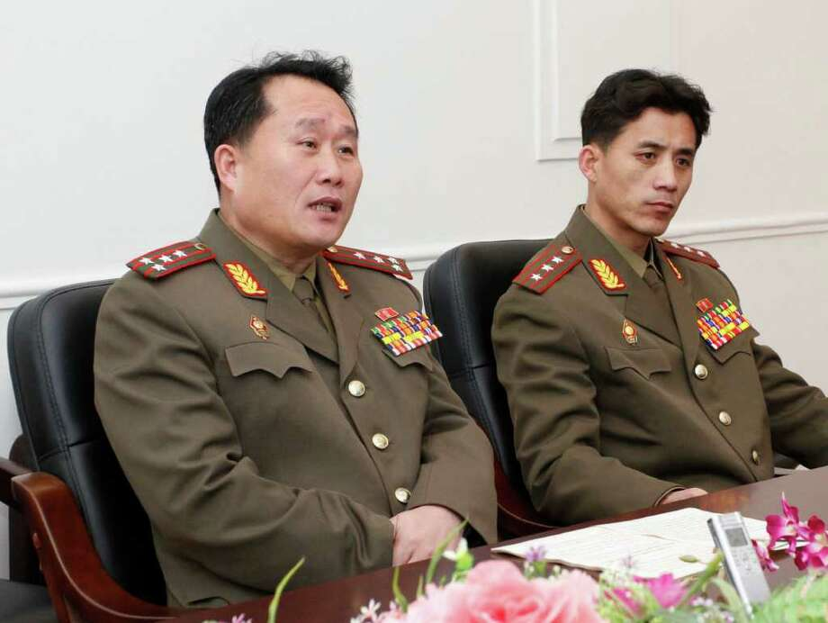 "Ri Son Kwon, left, a colonel working for the Policy Department of North Korea's National Defense Commission, accompanied by an unidentified official, speaks during an interview with The Associated Press in Pyongyang Thursday, Feb. 2, 2012. The powerful defense commission issued a list of nine conditions for resuming talks with the South, including demands that South Korea apologize for failing to show proper respect to Kim Jong Il during the mourning period that followed the leader's Dec. 17 death. ""If clear answers are given, dialogue will resume immediately, and the inter-Korean relations that have been moving toward complete destruction will improve,"" Ri told The AP. (AP Photo)"