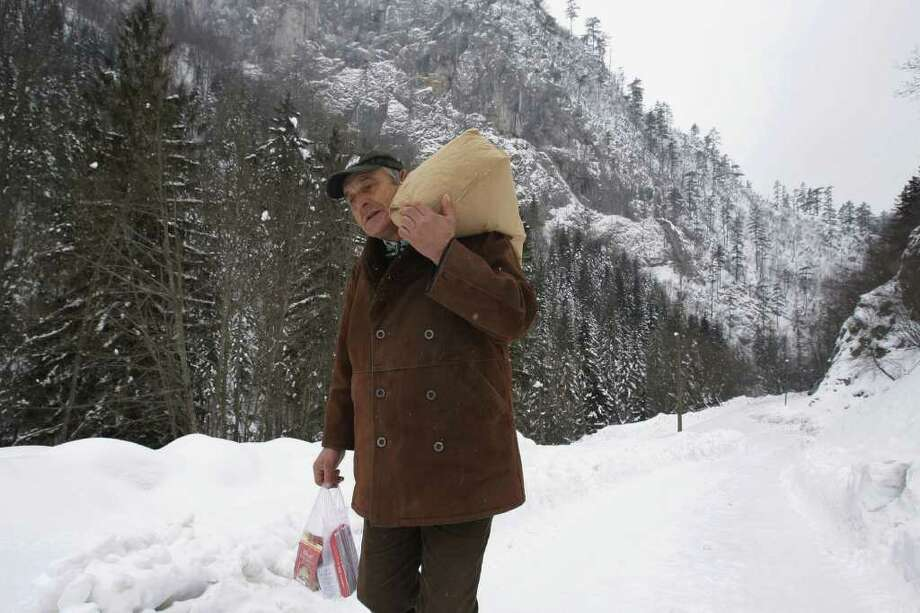 Bosnian Emin Hotovic, 55, carries a 25 kilo sack flour over shoulder and some groceries as he walks through thick snow to his remote village of Hotani, cut off by road, near the Bosnian town of Kladanj, 100 kms north of Sarajevo, Bosnia, on Thursday, Feb. 2, 2012. Rescue helicopters are airlifting supplies and evacuating dozens of people from snow-covered villages in Bosnia, as the death toll from Eastern Europe's severe cold spell has risen to 79. Central and eastern Europe are experiencing a severe and snowy cold snap with temperatures in Bosnia plummeting to lows of minus 10 Celsius (14 degrees Fahrenheit).(AP Photo/Amel Emric) Photo: Amel Emric / AP