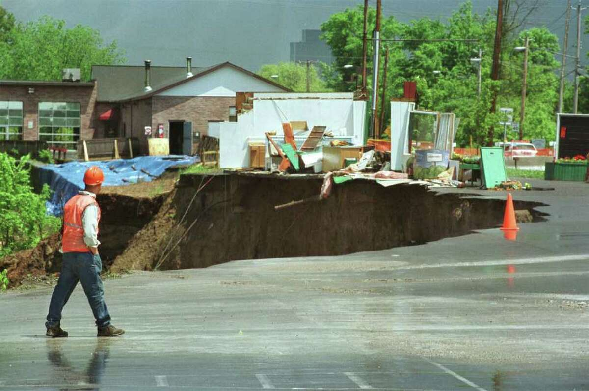 In May of 2000, 400 linear feet of earth, trees and shrubs detached from a rain-saturated hill behind a car wash in Bethlehem and fell to the Normans Kill ravine below. It destroyed a vegetable stand. Hoffman's Car Wash can be seen in the background. (Philip Kamrass/Times Union archive)
