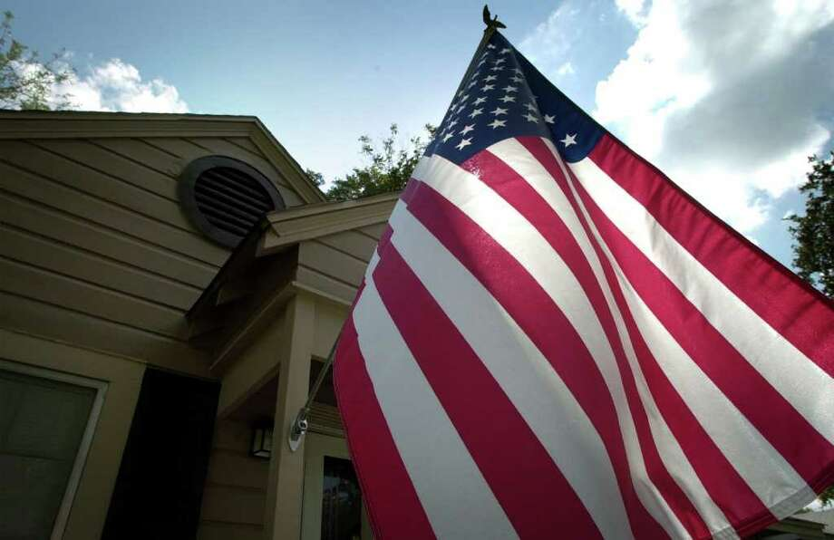 Under new laws the Texas Legislature passed last year, homeowners associations won't be able to keep members from displaying the U.S. or Texas flag, or flags of military branches. Photo: Bob Owen, San Antonio Express-News / en