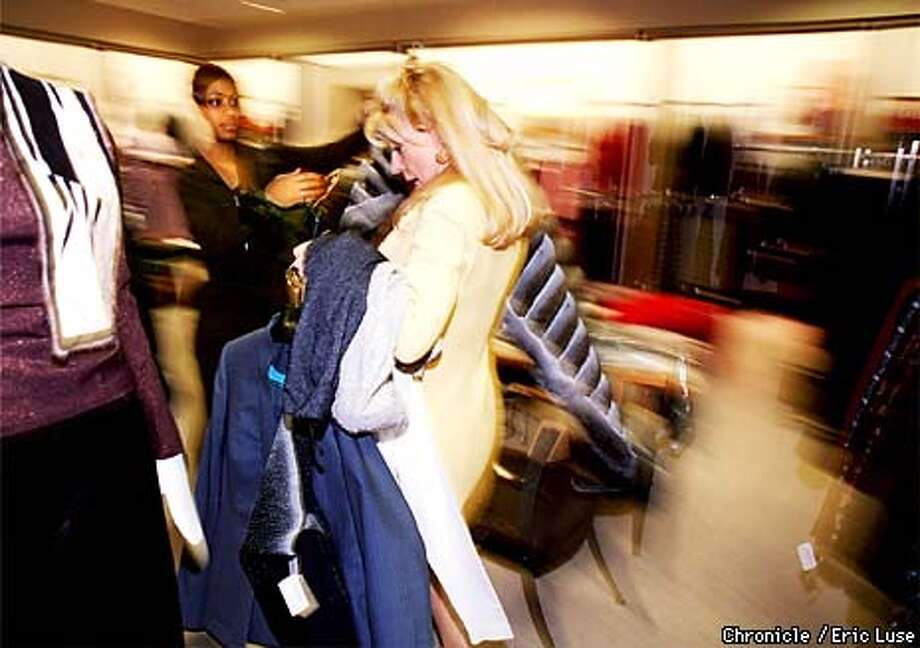 Katarina Cambron (right), saleswoman at Neiman Marcus hands off a load of clothes to her assistant Jamila Sherman she has brought in to show her client Linda Sheng who flew in from Taipei to shop. BY ERIC LUSE/THE CHRONICLE Photo: ERIC LUSE