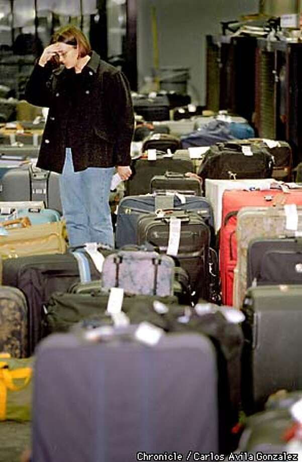 Kaytha Clawson, of Charleston, S. C., looks in vain for her baggage in one of the many piles at San Francisco Internation Airport on Tuesday, December 29, 1998. Clawson, who is originally from the Bay Area, was coming home for a vacaction, and got caught up in the problems the airport is having in the wake of the heavy fog hitting the area. (CHRONICLE PHOTO BY CARLOS AVILA GONZALEZ) Photo: CARLOS AVILA GONZALEZ