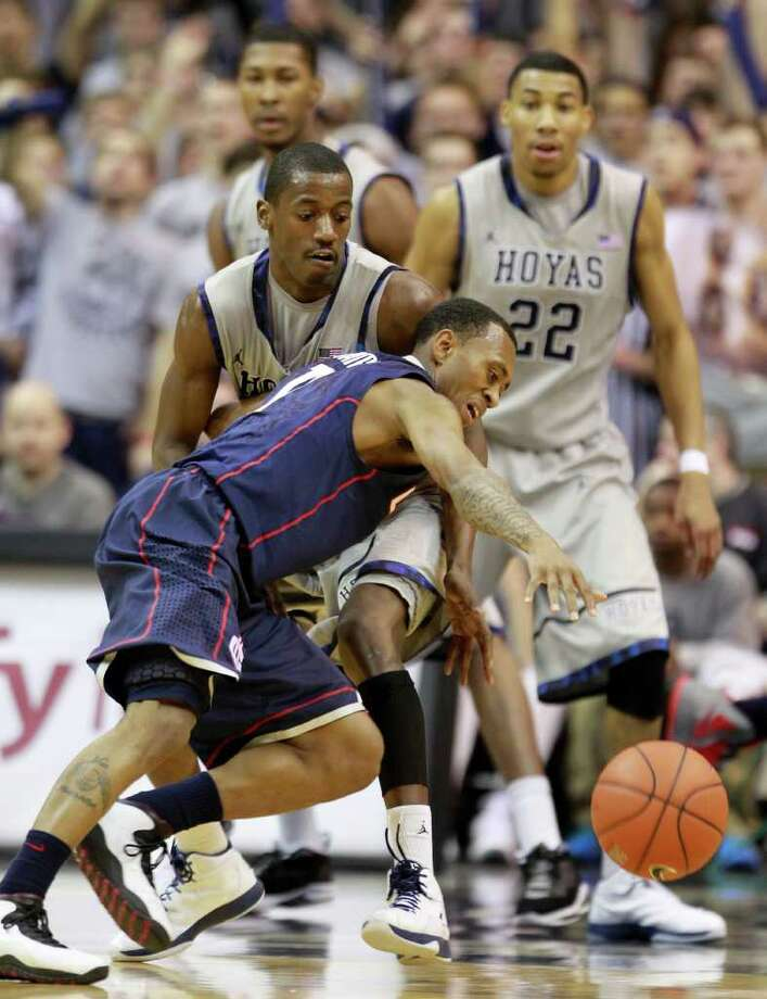 Connecticut's Ryan Boatright, front, reaches for a loose ball against Georgetown's Jason Clark as Georgetown's Otto Porter (22) and Mikael Hopkins, rear, look on, during the second half of an NCAA college basketball game  Wednesday, Feb. 1, 2012, in Washington. Georgetown won 58-44. (AP Photo/Haraz Ghanbari) Photo: Haraz Ghanbari, Associated Press / AP