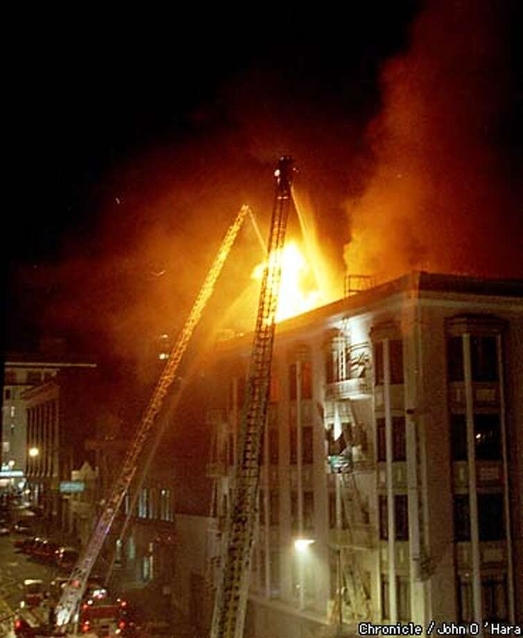 """Fire ! Four Alarm fire on Polk and Bush Sts.. Leland Hotel. The entire roof was burning, aquads of firefighters on the street while aerial ladders fought the fire.  photo by......John O'Hara Photo: John O""""Hara"""