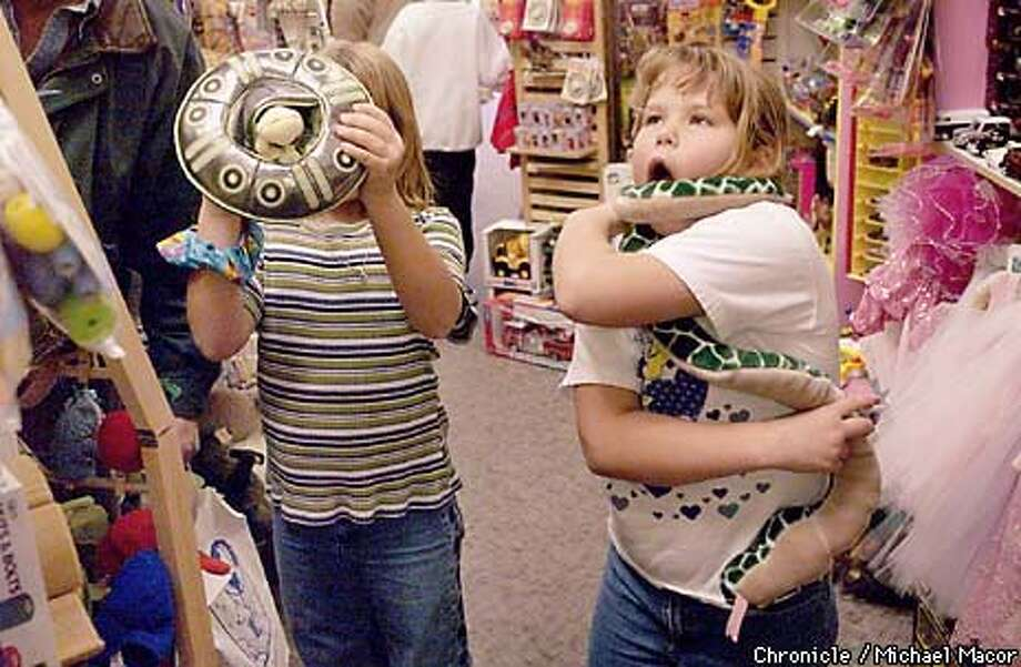 "At the ""Growing Up "" Toy Store twin sisters Kaylee, left and Amanda Thollander get sidetracked shopping for last minute gifts for other and find a few interested item for themselves. Kaylee with a UFO hat and Amanda pretends to get crushed by a stuffed snake. by Michael Macor/The Chronicle Photo: MCHALE MACOR"