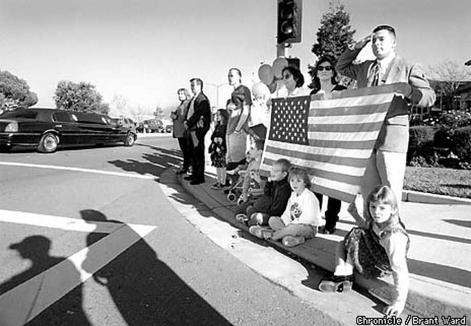 FUNERAL1/18DEC98/MN/BW--The citizens of Dublin and Pleasanton including Michael Urueta, far right saluting, crowded the sidewalks of Dublin Blvd as the remains of John Monego drove by in a hearse. By Brant Ward/Chronicle Photo: BRANT WARD