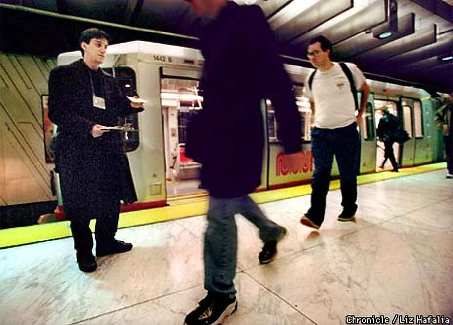 Nathan Bjorge (left) was passing out customer surveys at the Embarcadero Station. Muni Metro will be passing surveys out the next two weeks along their Market street stations to find out what riders think of Muni service. Photo by Liz Hafalia Photo: LIZ HAFALIA