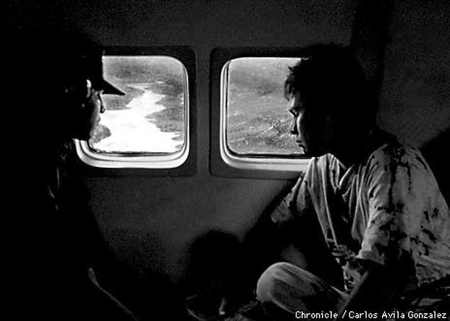 A Hoduran refugee and a Mexican Air Force crewmember look out the window of an evacuation plane at one of the swollen rivers near the town of Choluteca, Honduras on Saturday, November 7, 1998. The Mexican Air Force lent much support to the Honduran government to facilitate relief supply distribution, and to remove people from the devastated areas. (CHRONICLE PHOTO BY CARLOS AVILA GONZALEZ) Photo: CARLOS AVILA GONZALEZ