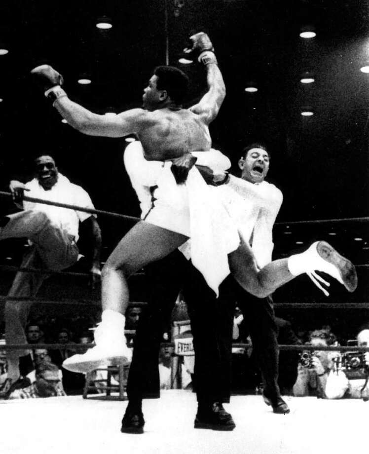 FILE - In this Feb. 25, 1964, file photo,  with flailing arms and legs, new heavyweight boxing champion Cassius Clay is lifted off the ring floor in Miami Beach by one of his handlers when Sonny Liston was unable the answer the bell for the seventh round. Another Clay handler, left, climbs through the ropes as trainer Angelo Dundee, right, reacts. Dundee, the trainer who helped groom Muhammad Ali (Clay) and Sugar Ray Leonard into world champions and became one of boxing's most recognizable figures, died Wednesday, Feb. 1, 2012. He was 90.  (AP Photo/hlv, File)
