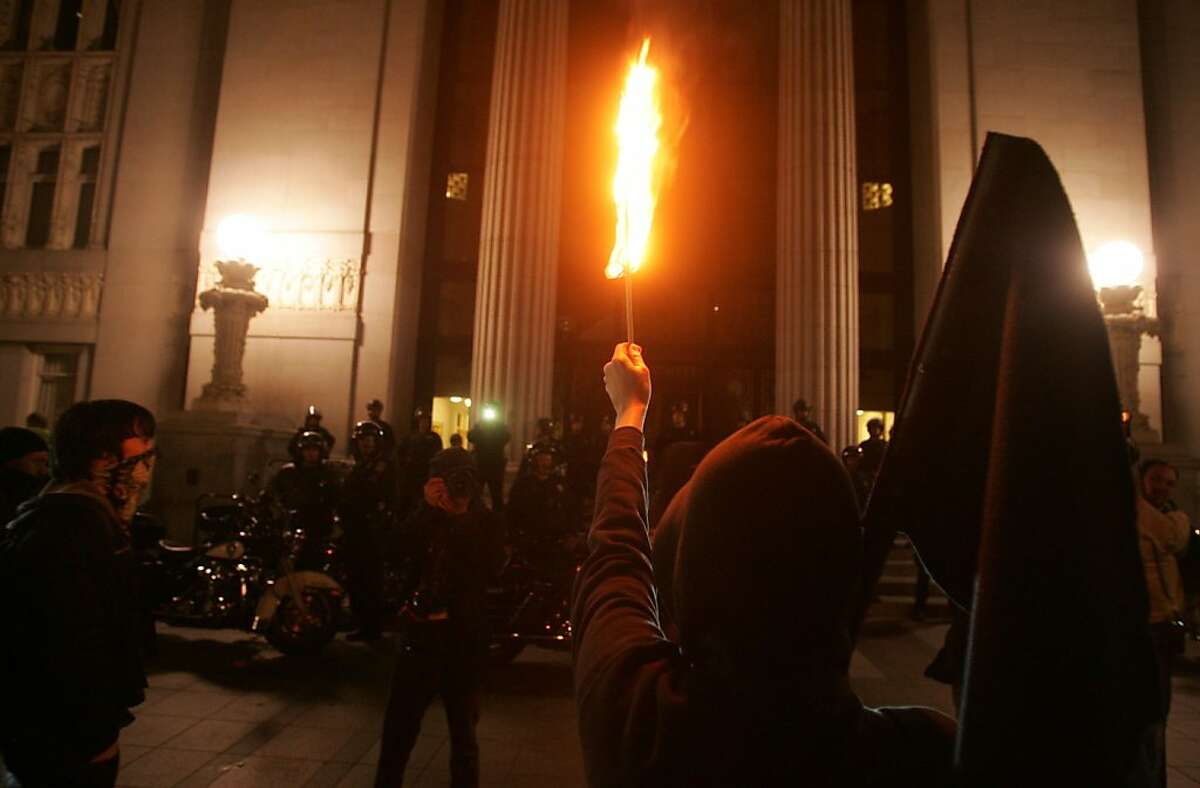 A protester burns a United States of America flag in front of city hall after a group of Occupy Oakland briefly broke into the building on Saturday, Jan 28, 2012 in Oakland Calif.