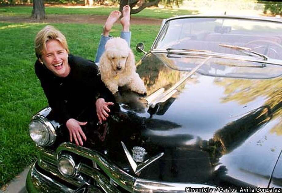 "Mary Bartnikowski, author of the book, ""Everyday Naked,"" sits on her 1950 Cadillac with Fluffy, her family's poodle. Bartnikowski has been compared to Erma Bombeck in her story-telling ability and the comical approach to everyday life's trials and tribulations. (CHRONICLE PHOTO BY CARLOS AVILA GONZALEZ) Photo: CARLOS AVILA GONZALEZ"