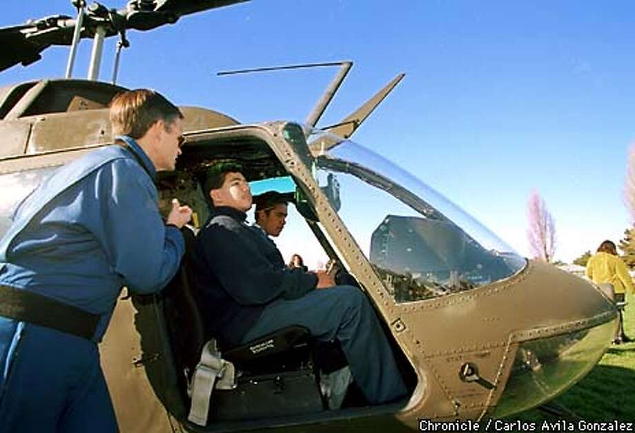 NASA Research Pilot Munro Dearing, (cq), shows off the interior of a NASA helicopter to Fernando Esquivel, center, and Siome Fusimalohi, during a demonstration at Edison McNair Academy in East Palo Alto on Monday, December 14, 1998. (CHRONICLE PHOTO BY CARLOS AVILA GONZALEZ) Photo: CARLOS AVILA GONZALEZ