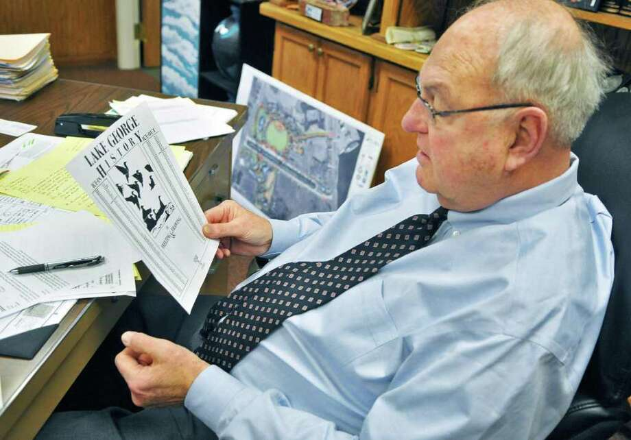Lake George Mayor Robert Blais reveiws the lake's ice-in ice-out history in his office in Lake George Village Thursday Feb. 2, 2012. This weekend's winter carnival is wrestling with a snowless, iceless winter.  (John Carl D'Annibale / Times Union) Photo: John Carl D'Annibale / 00016303A