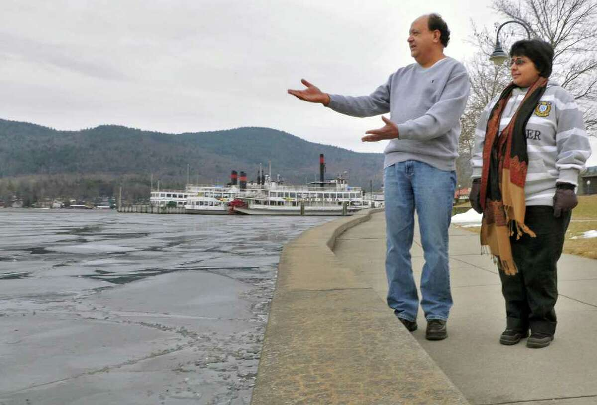 Mohammed,left, and Mussarat Tariq, owners of the Dory Motel,check out the very thin film of ice on Lake George Thursday Feb. 2, 2012. This weekend's winter carnival is wrestling with a snowless, iceless winter. (John Carl D'Annibale / Times Union)