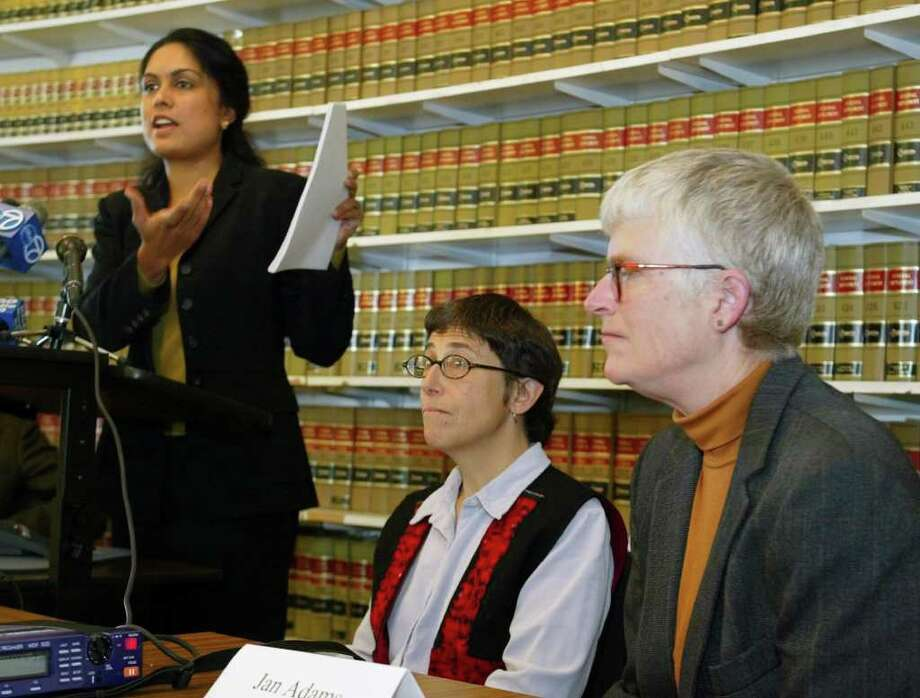 FILE - Jayashri Srikantiah, staff attorney with the ACLU of Northern California, holds up copies of records showing passengers checked on no fly lists from San Francisco International Airport, as plaintiffs Jan Adams, right, and Rebecca Gordon, center, look on during a news conference in San Francisco, in this April 22, 2003 file photo. The American Civil Liberties Union has sued the government on behalf of Americans who believe they're on the no-fly list and have not been able to travel by air for work or to see family. The no-fly list has swelled to 20,000 people before, such as in 2004. At the time, people like the late Sen. Ted Kennedy were getting stopped before flying _ causing constant angst and aggravation for innocent travelers. But much has changed since then.  (AP Photo/Eric Risberg, File) Photo: ERIC RISBERG