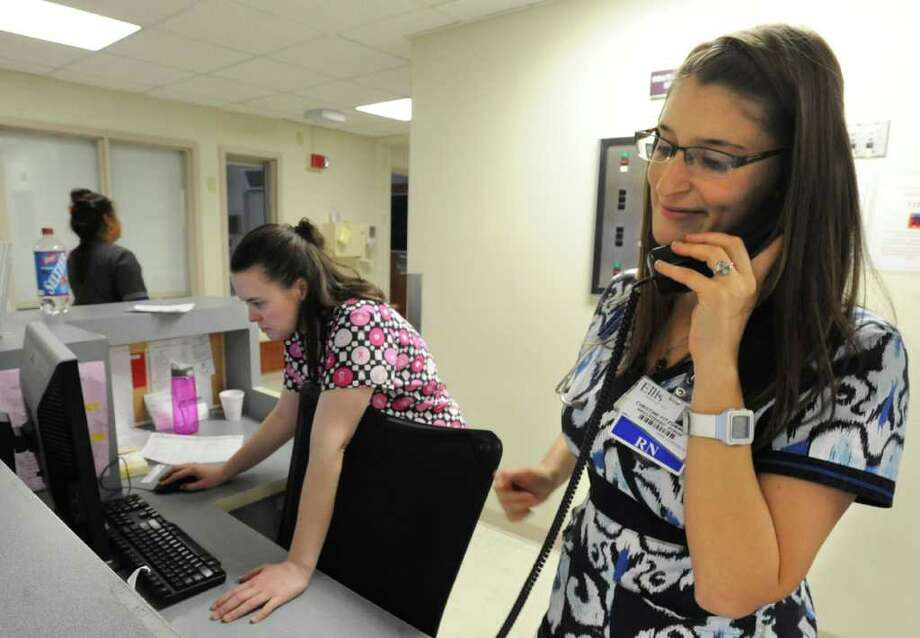 From left, Ellis Hospital nurses Amy Logan and Christine Fitzsimmons work at the nurses station in the neuroscience unit on Thursday, Feb. 2, 2012 in Schenectady, N.Y. Both nurses are new to the hospital as of last year. This is Amy's first career right out of nursing school and Christine was an actor in the theater in Manhattan. (Lori Van Buren / Times Union) Photo: Lori Van Buren