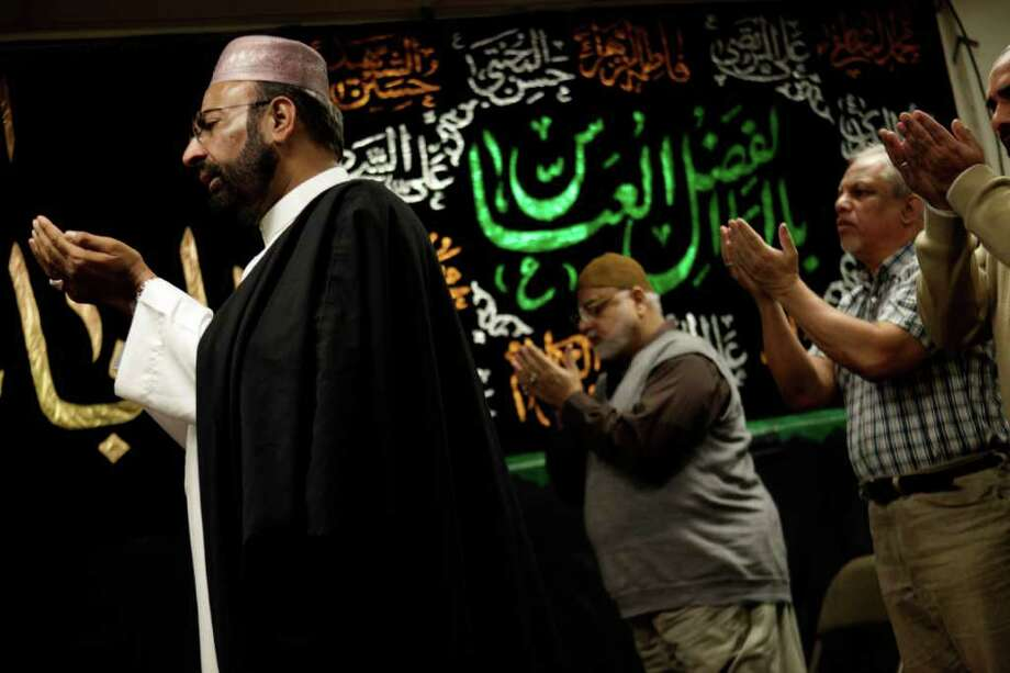 Imam Malik Sakhawat Hussain, left, leads prayers at the Al-Mahdi Foundation in New York, Wednesday, Feb. 1, 2012.  As it canvassed the Northeast looking for Iranian terrorists, the New York Police Department recommended increasing surveillance of thousands of Shiite Muslims and their mosques based solely on their religion, according to interviews and a newly obtained secret police document. The document offers a rare glimpse into the thinking of NYPD intelligence officers and how it drove the department's aggressive spying operations. The Associated Press has reported for months that the NYPD infiltrated mosques, eavesdropped in cafes and monitored entire Muslim neighborhoods with plainclothes officers.  (AP Photo/Seth Wenig) Photo: Seth Wenig