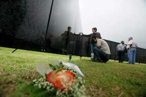 Ernest (crouching) and Melinda Trevino look Thursday for names of troops they knew who were killed in the Vietnam War as they visit The Wall That Heals at Lackland AFB Thursday, Feb. 2, 2012. The exhibit is a half-size replica of the Vietnam Veterans Memorial in Washington, D.C., and it travels around the country. Ernest Trevino served in the Army and was in Vietnam in 1968 and 1969.