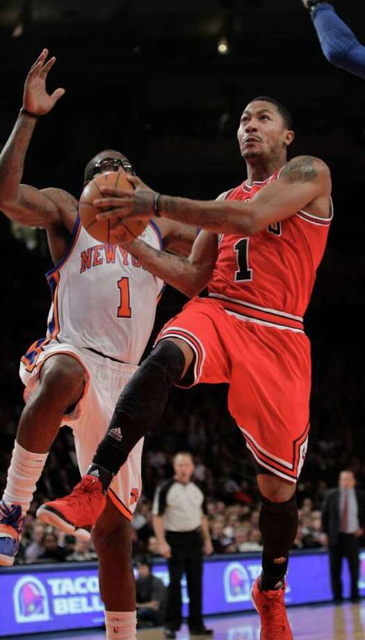 Chicago Bulls guard Derrick Rose (1) goes up for a layup in front of New York Knicks forward Amare Stoudemire (1) in the third quarter of their NBA basketball game at Madison Square Garden in New York, Thursday, Feb. 2, 2012. The Byulls defeated the Knicks 105-102. (AP Photo/Kathy Willens) Photo: Kathy Willens