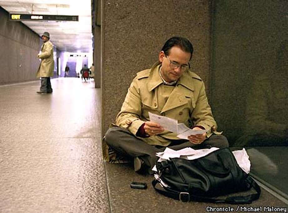 Robert Moore, an environmental consultant takes care of paperwork at the Embarcadero BART station. He was waiting for the trains to start again. He neede to get to the eastbay for an appointment.  Photo by Michael Maloney Photo: MICHAEL MALONEY