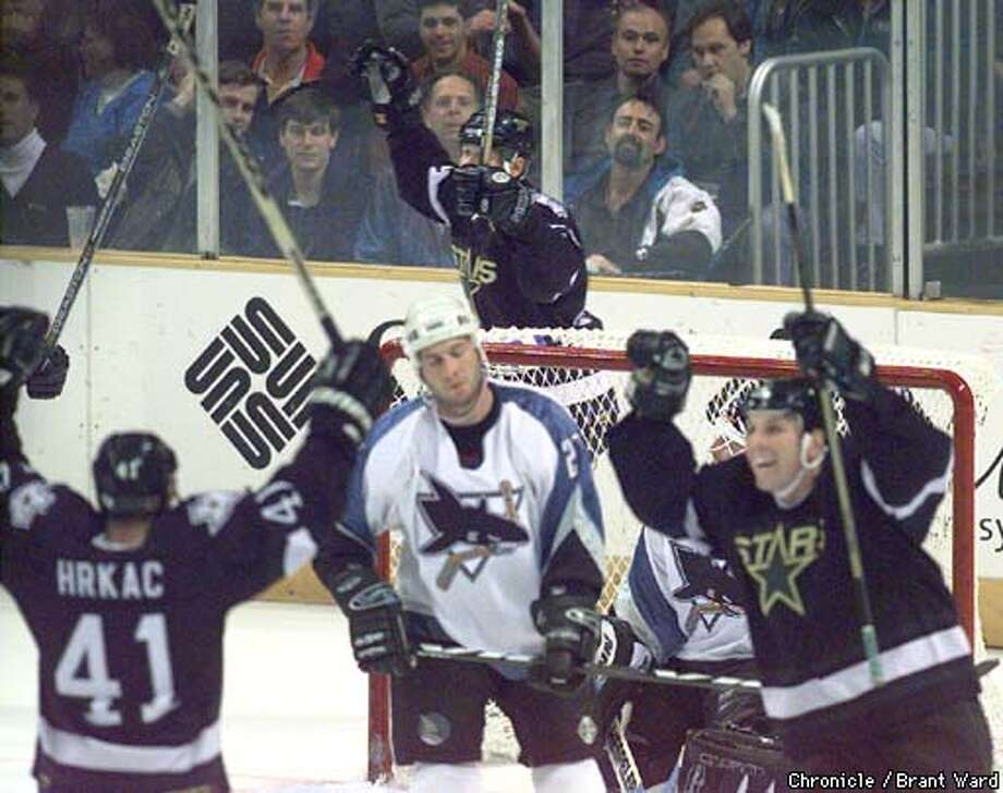 STARS JUBE/02DEC98/SP/BW--The Sharks Bryan Marchment looks stunned as the Stars celebrated their third goal of the first period. Tony Hrkak, far left, had two of the first period goals off goalie Mike Vernon. By Brant Ward/Chronicle Photo: BRANT WARD