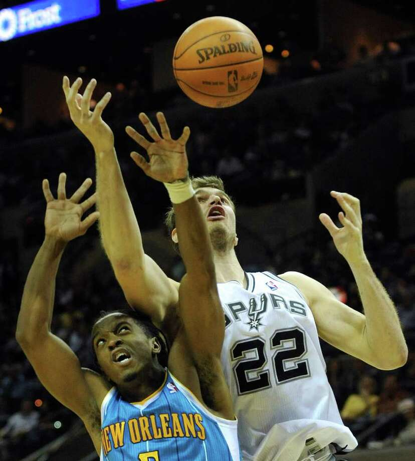 Tiago Splitter of the San Antonio Spurs (22) battles Carldell Johnson of the New Orleans Hornets at the AT&T Center on Thursday, Feb. 2, 2012.  Billy Calzada / San Antonio Express-News