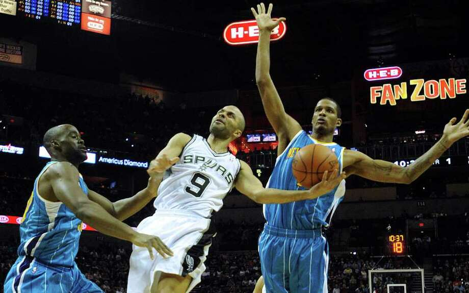 Tony Parker of the San Antonio Spurs (9) shoots a layup as Emeka Okafor, left, of the New Orleans Hornets, and Trevor Ariza, right, defend on Thursday, Feb. 2, 2012.  Billy Calzada / San Antonio Express-News  New Orleans Hornets at San Antonio Spurs Photo: Billy Calzada, Express-News / San Antonio Express-News