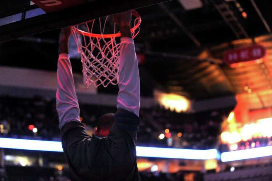 Tim Duncan of the Spurs hangs, as is his custom, from the rim when the lights are turned down for players introductions at the AT&T Center on Thursday, Feb. 2, 2012.  Billy Calzada / San Antonio Express-News