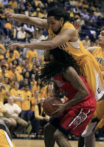 Arizona forward Jesse Perry, bottom, looks to shoot as California guard Jorge Gutierrez jumps over him during the first half of an NCAA college basketball game in Berkeley, Calif., Thursday, Feb. 2, 2012. Photo: Jeff Chiu, Associated Press
