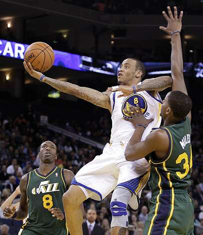 Golden State Warriors' Monta Ellis (8) lays up a shot against Utah Jazz' Josh Howard, left, and C.J. Miles (34) during the second half of an NBA basketball game Thursday, Feb. 2, 2012, in Oakland, Calif. (AP Photo/Ben Margot) Photo: Ben Margot, Associated Press