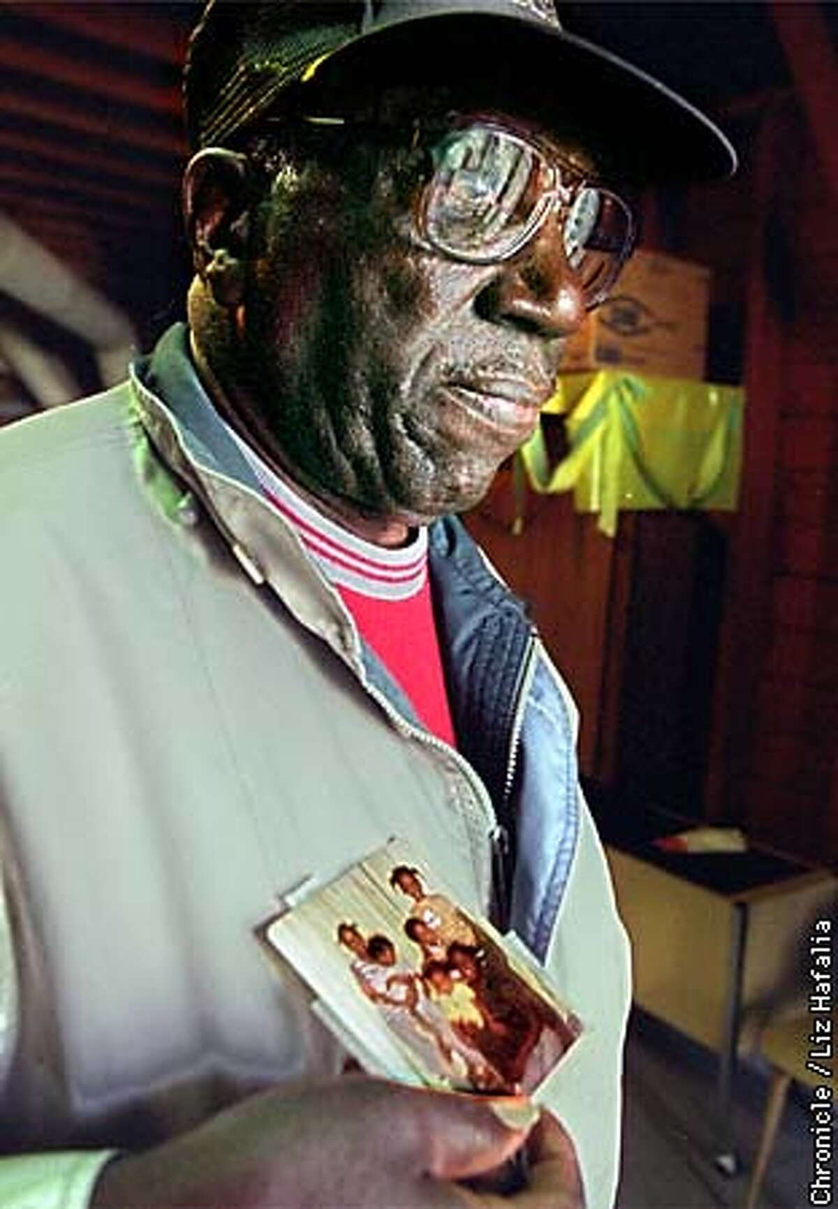 LEWIS /C/04NOV98/MN/LH--Freddie Lewis holding his one picture showing six of his seven children who were killed in the mass suicide ordered by Jim Jones twenty years ago. His wife as well as nineteen of his relatives were also part of the mass tragedy. Photo by Liz Hafalia