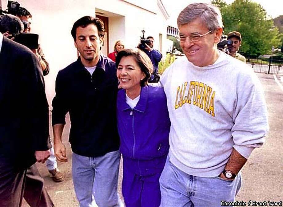BOXER VOTE/03NOV98/MN/BW--Senator Barbara Boxer left her voting place in Greenbrae Tuesday morning with son Doug, left, and husband Stewart helping her negotiate the press that had gathered. Boxer said she will wait out the vote at her Marin County home. By Brant Ward/Chronicle Photo: BRANT WARD