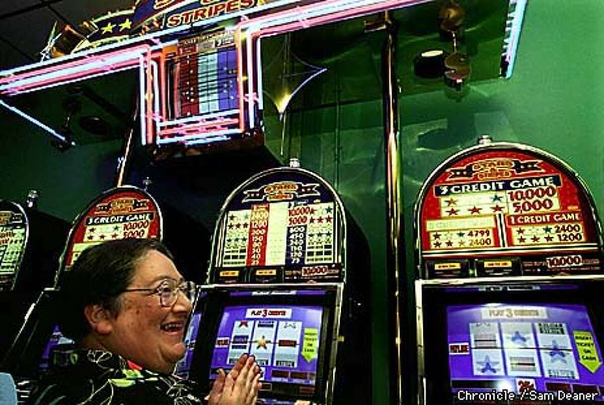 Norma McGarr, a tribal spouse with the Pala Band of Mission Indians, is elated she won 75-cents on her first experience gambling with an Electronic Video Gaming Machine Thursday at the Jackson Rancheria Indian Bingo and Casino in Jackson, California. Lottery Gaming control results for draws are displayed on the video screen overhead. (Chronicle photo/ Sam Deaner)