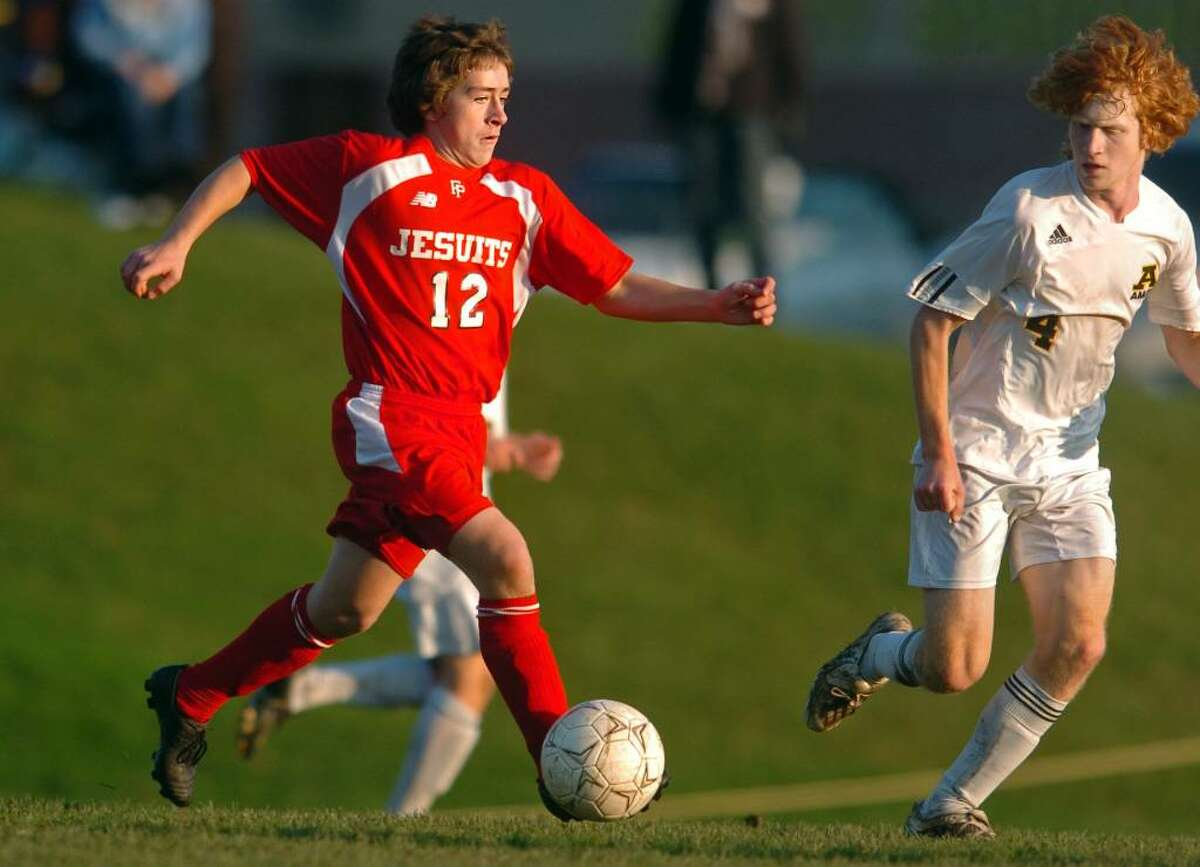 Fairfield Prep's David Bruton drives the ball down the field as Amity's Josh Brunwin defends during the second half of Tuesday's SCC semifinal game in Woodbridge.