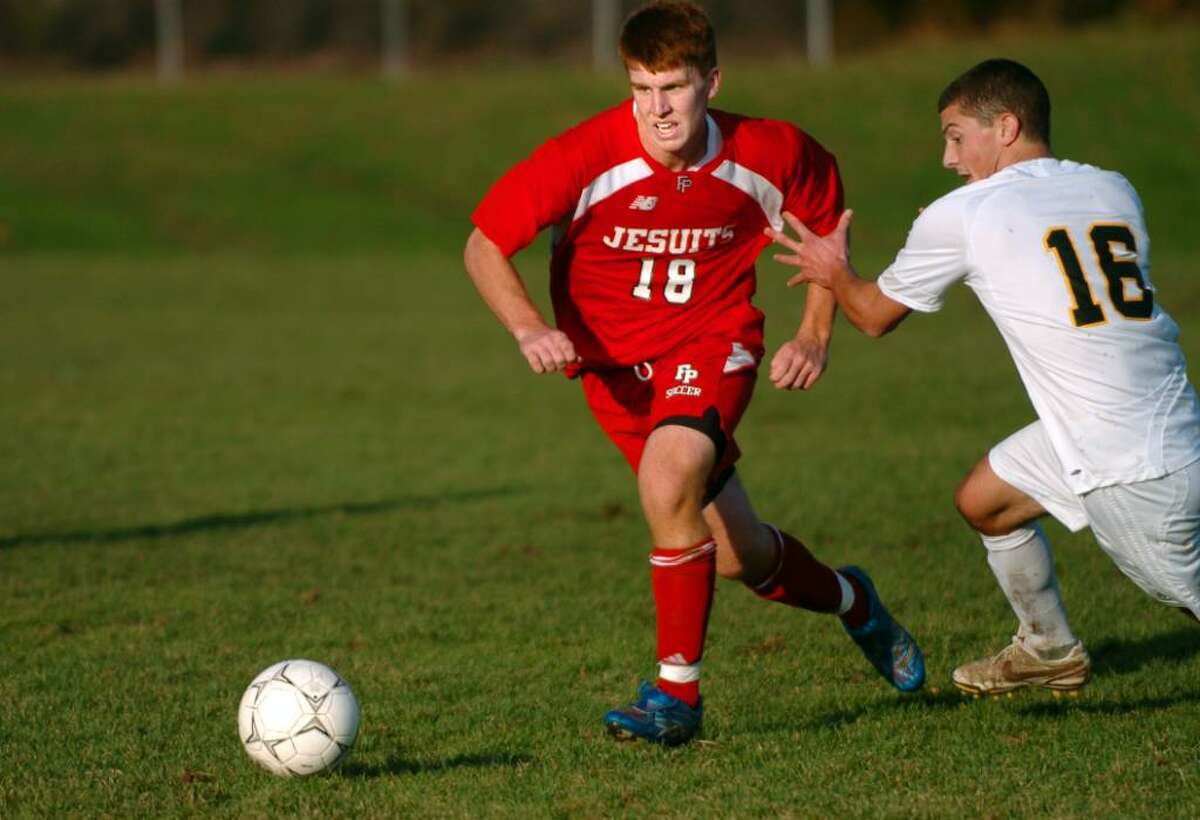 Fairfield Prep's Matthews D'Ambrisi controls the ball as Amity's Joshua DeBarba defends during the second half of Tuesday's SCC semifinal game in Woodbridge.