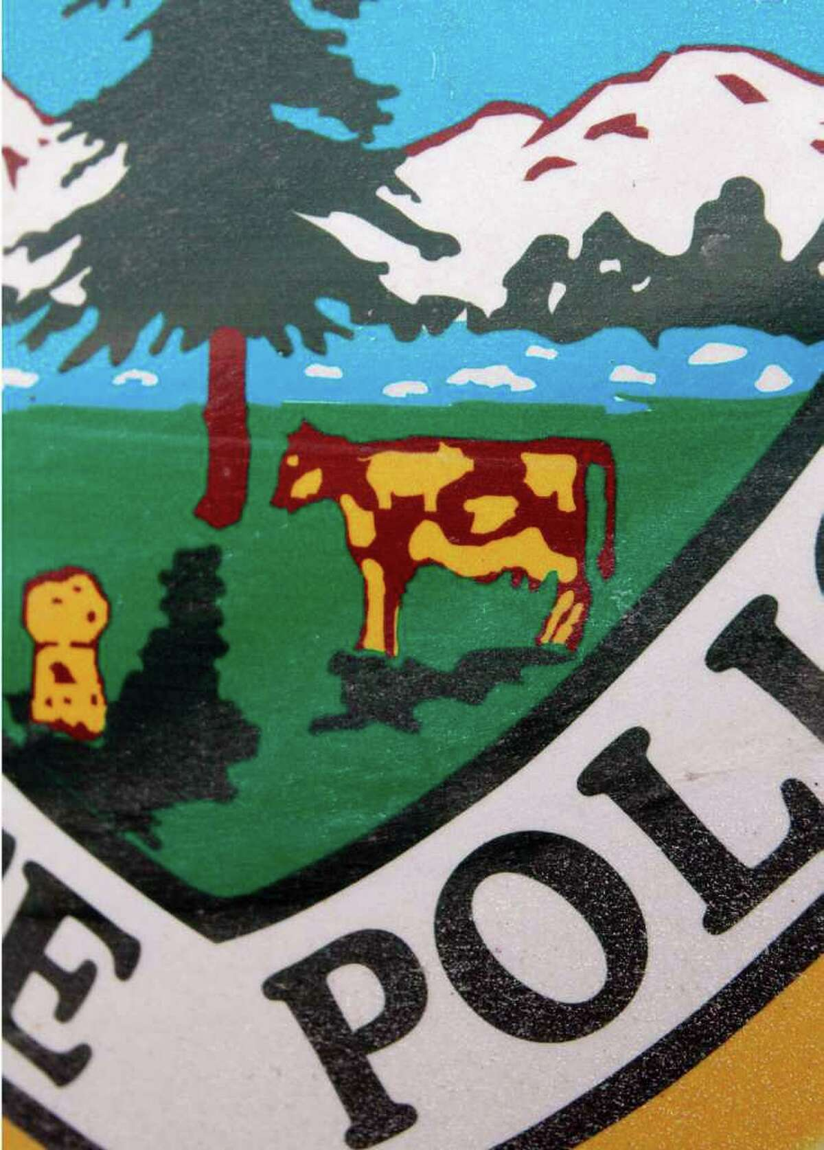 The state seal is seen on the side of a Vermont State Police cruiser Thursday, Feb. 2, 2012 in Middlesex, Vt. Some Vermont inmates have gotten the best of the state police by adding a pig to the state decal on their cruisers. One of the spots on the cow in the state crest has been changed to the shape of a pig, a derogatory term for police. The car decals are made by prisoners in St. Albans, who also make state stationary and license plates. (AP Photo/Toby Talbot)