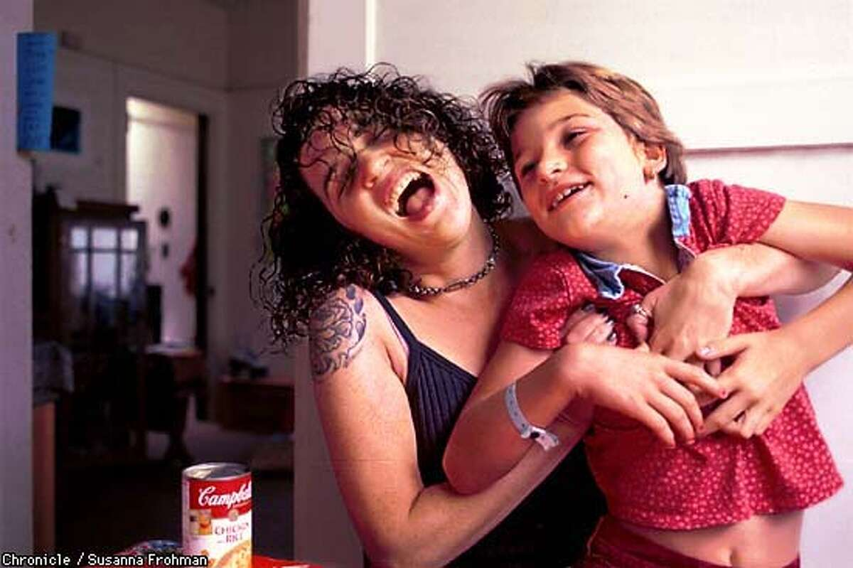 Aerial Gore, author of the Hip Mama Survival Guide, laughs with her 8-year old daughter Maia Swift at their home in Oakland. (CHRONICLE PHOTO BY SUSANNA FROHMAN)