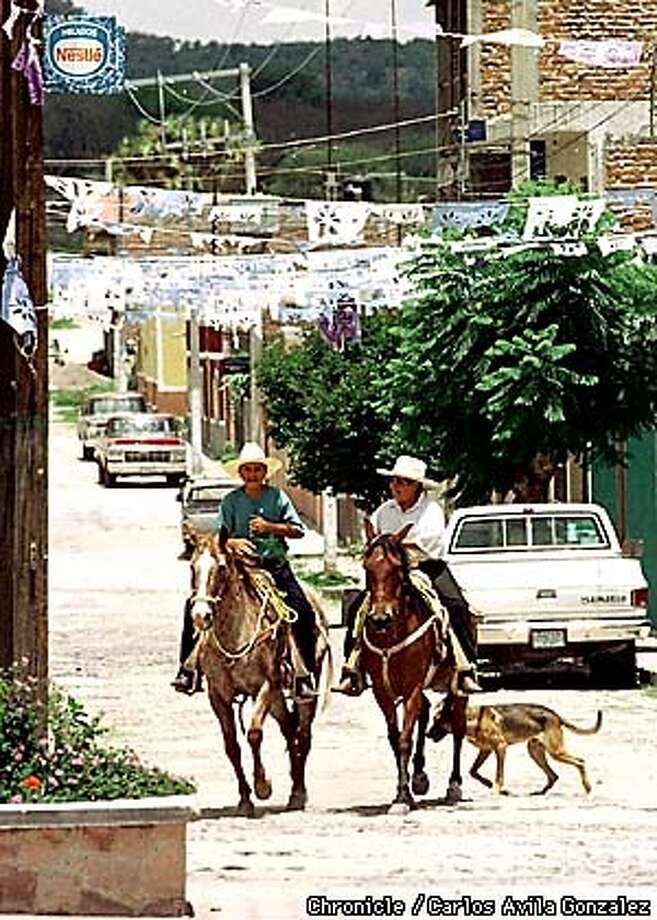 Two young men ride their horses down the main street leading into Tlacuitapa, Jalisco, a town where many of the residents have emigrated to Union City, Ca. In a few years, these two may one day join the hundreds of others from their small towns to make the trip up north. (CHRONICLE PHOTO BY CARLOS AVILA GONZALEZ) Photo: CARLOS AVILA GONZALEZ