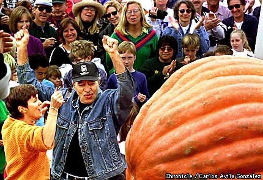 Pete Glasier and his wife, Cindi Glasier, of Napa celebrate in the final minutes of the Half Moon Bay Pumpkin Weigh Off on Monday, October 12, 1998. In the final minutes of the Weigh Off, Glasier's pumpkin took the lead with a weight of 825 pounds. But his celebration didn't last long, as the largest pumpkin came to the scale just minutes later, weighing in at 974 pounds. (CHRONICLE PHOTO BY CARLOS AVILA GONZALEZ) Photo: CARLOS AVILA GONZALEZ