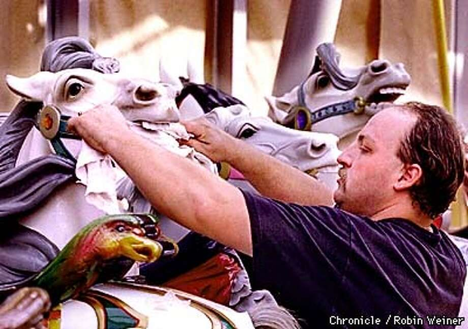 Steve Simmons of Berkely uses a towel to wipe the dust inside the mouth of a carousel horse during the installation of the 1906 vintage Charles Looff Carousel at The Rooftop at Yerba Buena Gardens in preparation for the Oct. 17th grand opening.  BY ROBIN WEINER/THE CHRONICLE Photo: ROBIN WEINER