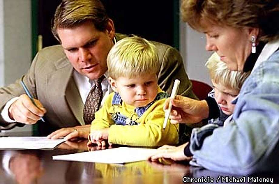 Ken and Leslie Barrentine and their kids Wes (2) and Vincent (4) sign refinance papers for their home loan. The Barrentine's are from Concord and were in the SF office of Jesse Jones, of First American Title Company. BY MICHAEL MALONEY/THE CHRONICLE Photo: MICHAEL MALONEY