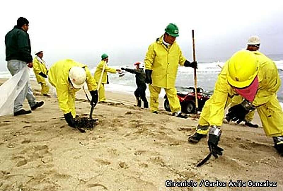 A work crew with FOSS Environmental Services of Alameda cleans up tar balls on Thursday, October, 1, 1998 that washed ashore at Pomponio State Beach along the San Mateo Coast after oil from an oil spill finally came ashore Wednesday night. (CHRONICLE PHOTO BY CARLOS AVILA GONZALEZ) Photo: CARLOS AVILA GONZALEZ