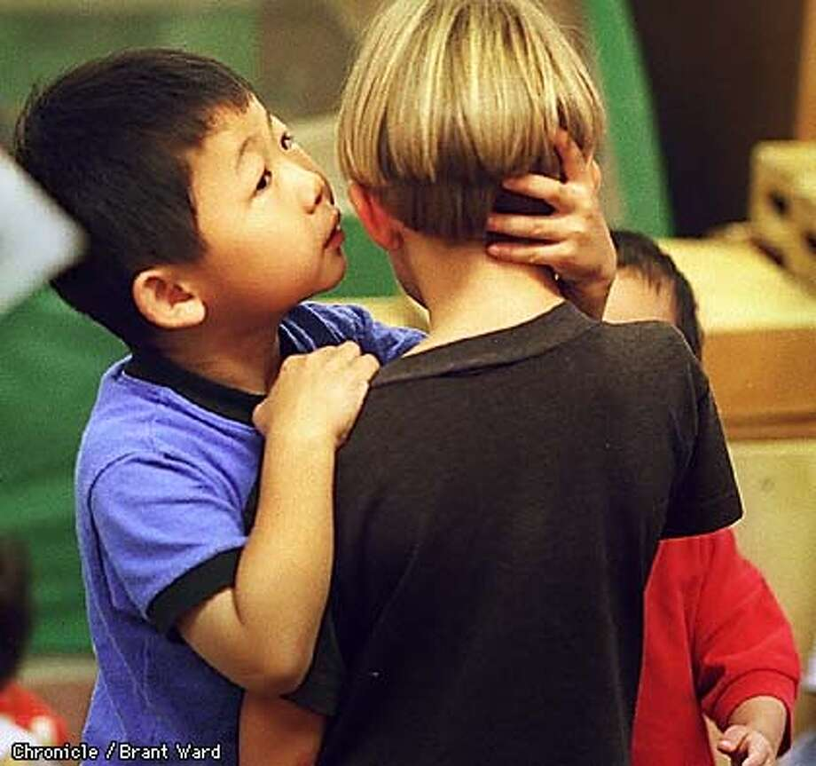 PRESCHOOL1/24SEP98/MN/BW--Wei Wei Long, left, whispers in the ear of his old friend Dante Graziose at the College of Marin preschool. By Brant Ward/Chronicle Photo: Brant Ward