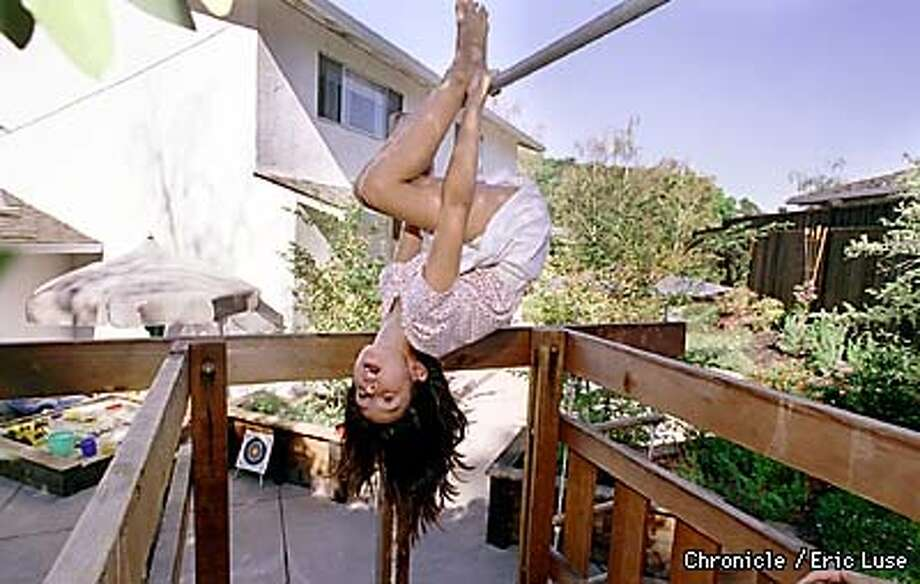 Alexa Stevens,7, hangs upside down in her San Rafael backyard fort.  BY ERIC LUSE/THE CHRONICLE Photo: ERIC LUSE